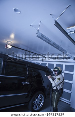Side view of middle aged traffic cop aiming revolver while standing by car in garage