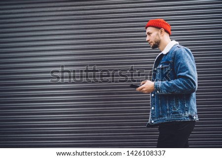 Side view of millennial man dressed in trendy jeans jacket walking near promotional background with copy space for fashion advertising, Caucasian male generation with gadget at publicity area