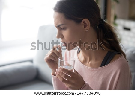 Side view of millennial unhappy stressed multiracial woman sitting on couch, taking white round pill and holding glass of fresh water, completion of early pregnancy or sharp ache reducing painkiller.