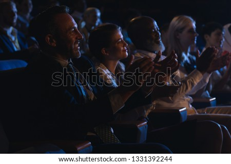 Side view of mixed race business colleagues sitting and watching presentation with audience and clapping hands