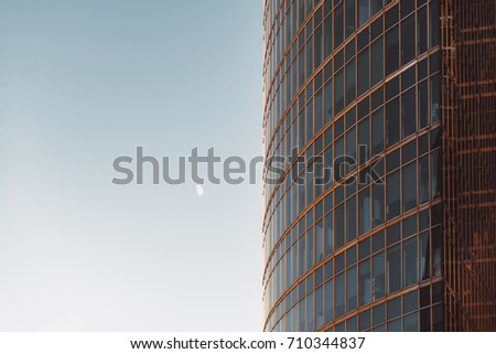 "Side view of modern skyscraper teal and orange glassy facade with blue sky and moon on other side, offices overlooked behind windows, ""Moscow City"" business skyscrapers group, Russia #710344837"