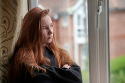 Side view of moody female teenager in black casual wear with red hair standing at window with arms crossed and looking away while staying at home under isolation