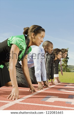 Side view of multi ethnic business people at starting line on race track