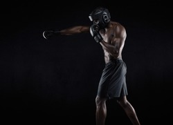 Side view of muscular man boxing on black background. Afro american young male boxer practicing shadow boxing.