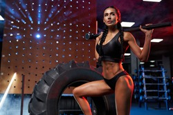 Side view of muscular woman in black sports underwear holding sledgehammer on shoulders behind head, leg on giant tire wheel. Stunning female bodybuilder posing in gym, colorful lights.
