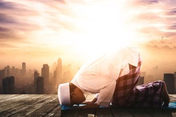 Side view of Muslim man is doing Salat with prostration pose in silhouette of city background at sunset time