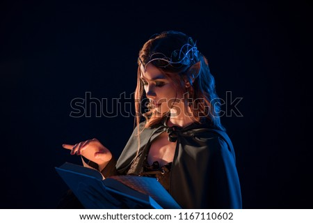 Side view of mystic female beatiful elf reading magical book in darkness. Girl having long vawy hair, pretty face features, plump lips, big eyes, wearing cape on shoulders, elegant, thin crown.