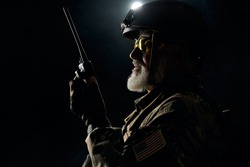 Side view of old military soldier in uniform holding portable radio station in darkness. Close up of male commander in camouflage uniform giving orders. Concept of army, military.