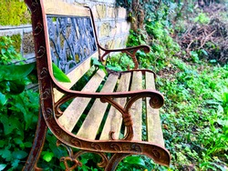 Side view of old wooden and metal bench in garden