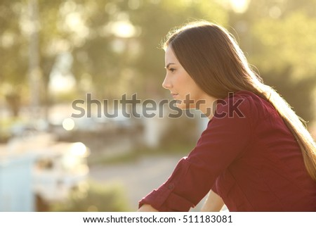 Side view of one angry woman thinking and looking away in a house balcony at sunset