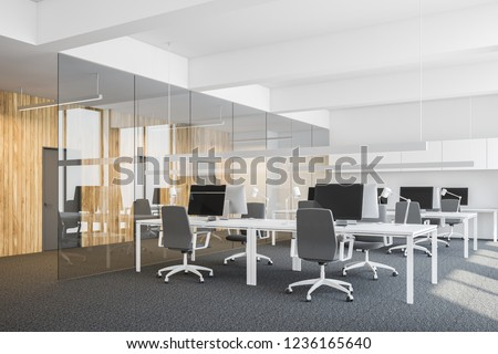 Side view of open space office with white walls, carpet on the floor, rows of computer tables and row of closed doors in wooden wall. 3d rendering