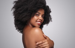 Side view of optimistic African American female smiling for camera and touching shoulder after spa procedure against gray background