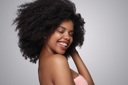 Side view of optimistic African American lady smiling with closed eyes and touching clean curly hair while representing spa service against gray background