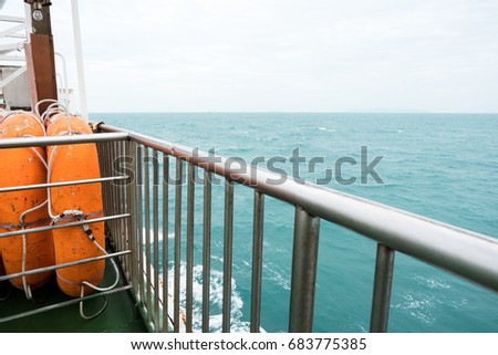 Side view of orange lifeboat steel fence and barrier to prevent passengers falling from boat. Small craft aboard a ship to allow for emergency escape and this boat designed for sea rescues.