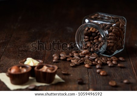 Side view of overturned glass jar with coffee beans and chocolate candies on wooden background, selective focus #1059496592