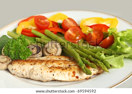 Side view of pan-fried fish, served with boiled asparagus and mushrooms and a salad of lettuce, rocket, capsicum and tomato, garnished with a sprig of parsley