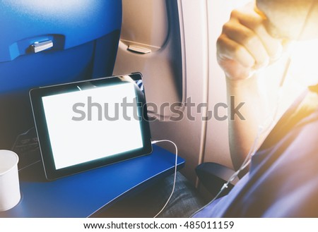 Side view of passenger traveler tourist using tablet at salon airplane. Female hands texting message on gadget on background window aircraft, summer traveler journey trip concept, mockup blank screen