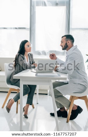 side view of patient and doctor talking in clinic with laptop on table