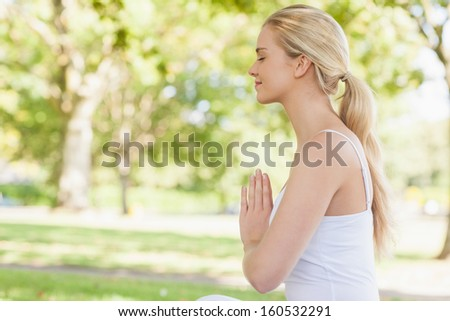 Side view of peaceful young woman meditating sitting in park with closed eyes - Shutterstock ID 160532291