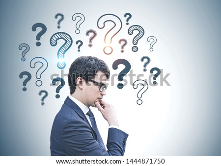 Side view of pensive young caucasian businessman wearing dark suit and glasses and standing near gray wall with question marks drawn on it. Concept of planning