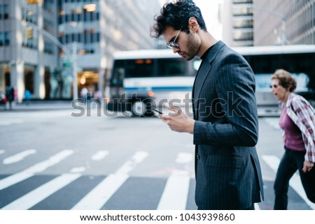 Side view of pensive young entrepreneur in stylish suit reading financial news in mobile application crossing zebra in downtown of metropolis.Confident proud CEO checking banking account on cellular #1043939860