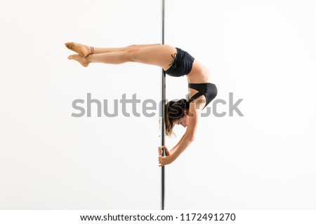 Side view of pole dancer practicing crescent moon pose against white background