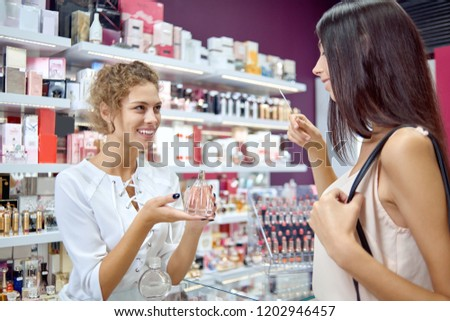Side view of polite female consultant helping customer with choice in cosmetics store. Young brunette smelling different perfumes before purchasing in shop. Concept of shopping and buying.
