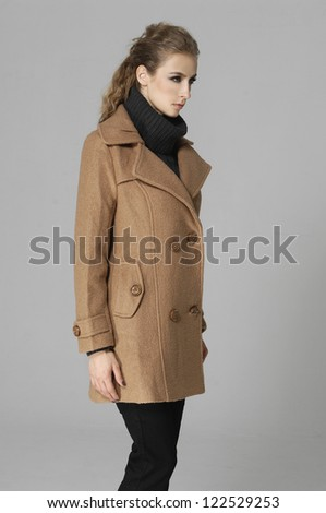Side view of portrait of young girl in coat isolated on gray background