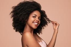 Side view of positive African American female model smiling for camera and touching clean curly hair after hygienic routine against brown background