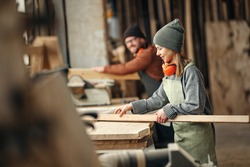 Side view of positive young female woodworker in apron working with lumber in carpentry workshop with colleague