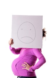 Side view of pregnant woman holding sign with a sad smiles face
