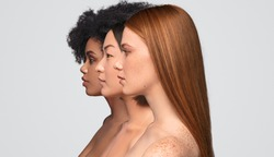 Side view of pretty diverse ladies with clean skin standing in row while representing skincare industry against gray background