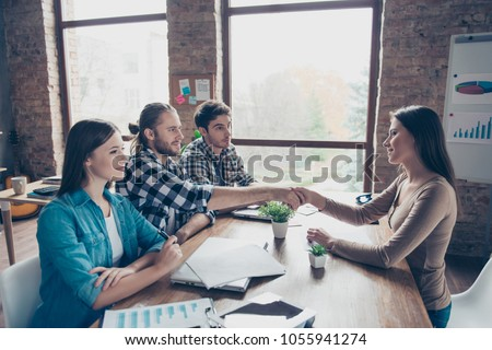 Side view of pretty hr manager recruiting new worker in company, making handshake with bearded man, conclude a contract