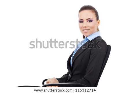 side view of pretty young business woman sitting on an office chair and smiling at the camera