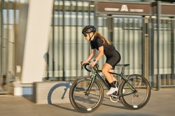 Side view of professional female cyclist in black cycling garment and protective gear riding bicycle in city, rushing and passing outdoors on a sunny day