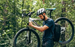Side view of professional male cyclist cycling on mountain road on nature background. Young man bicyclist taking the bike in the forest outdoor.