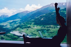 Side view of prosperous digital nomad celebrating lottery online win during networking time on modern laptop computer, happy excited female with raised hands reading good news about business triumph
