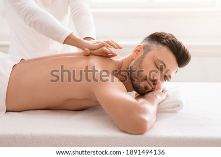 Side view of relaxed handsome man having body massage at spa salon. Middle aged bearded man attending modern male spa, laying on massage table, getting healing body procedure, enjoying his day at spa