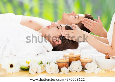 Side view of relaxed young couple receiving head massage at beauty spa #370029122