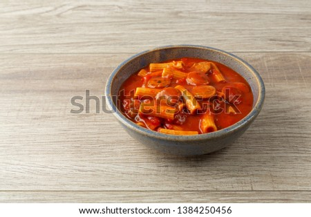 Side view of rigatoni pasta and sausage in an old stoneware bowl on a tile table illuminated with natural lighting.
