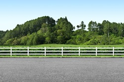 Side view of road, white fence and landscape