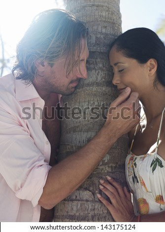 Side view of romantic young couple by tree trunk at beach