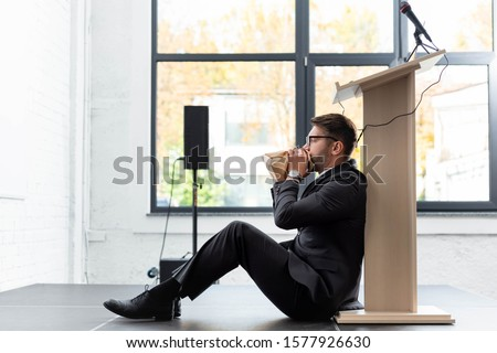 side view of scared businessman in suit breathing in paper bag during conference Foto stock ©
