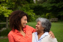 Side view of senior African American woman with her daughter in the garden, smiling at each other and embracing. Family enjoying time at home, lifestyle concept