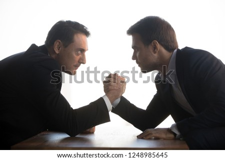 Side view of senior aged and millennial young businessmen in formal suits holds elbows on table arm wrestling at office workplace looking eyes to eyes face to face struggling for leadership at work