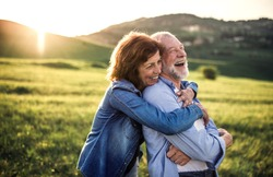 Side view of senior couple hugging outside in spring nature at sunset.