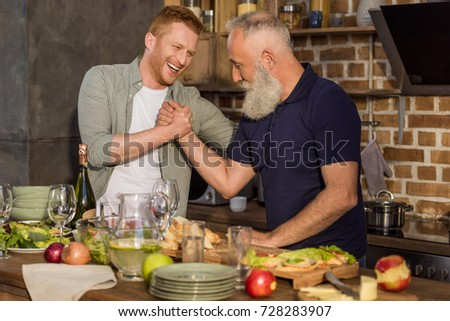 side view of senior father and adult son arm wrestling together in kitchen at home