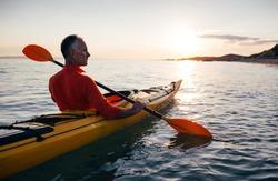Side view of senior man paddling kayak on the sunset sea