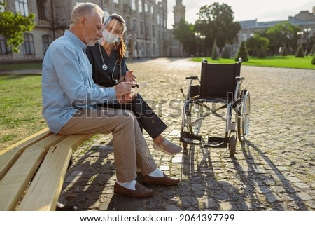 Side view of senior man recovering patient talking to nurse wearing face shield, sitting together on the bench near rehabilitation clinic