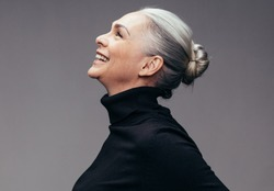 Side view of senior woman laughing on gray background. Profile view of mature woman in black casuals looking happy